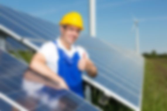 Photovoltaic engineer showing thumbs up at solar panel array